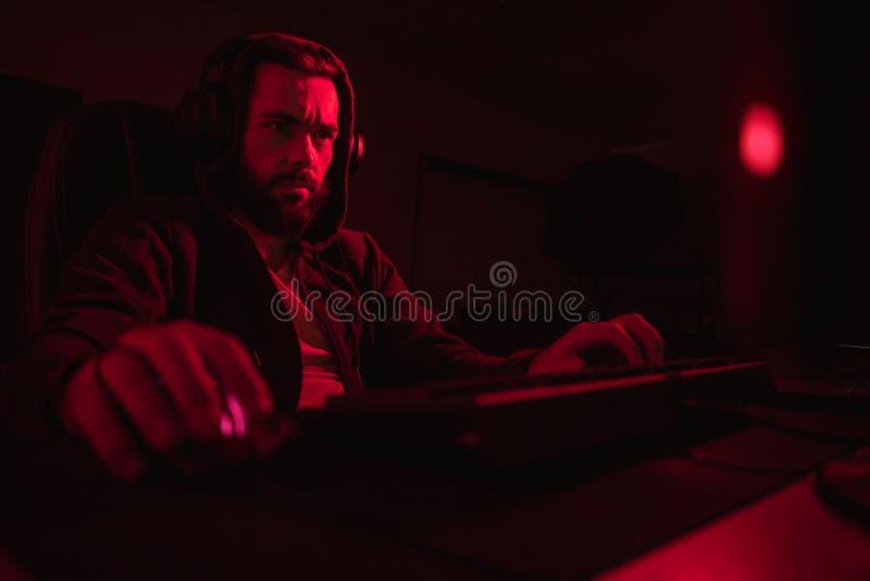 Pirata informatico barbuto che per mezzo del computer immagine stock