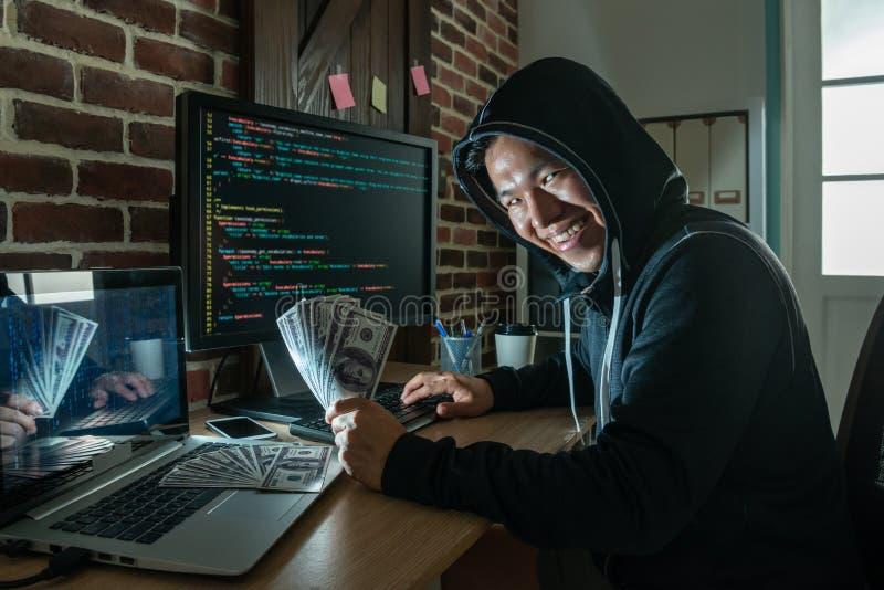 Pirata informatico che guarda in tondo e che tiene banconota fotografia stock libera da diritti