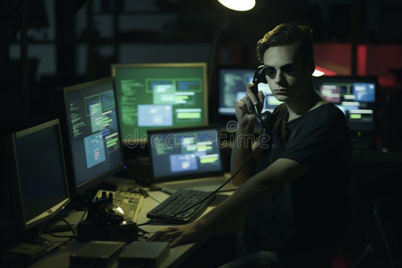 Pirata informatico che hoding un ricevitore e gli schermi di computer immagine stock libera da diritti