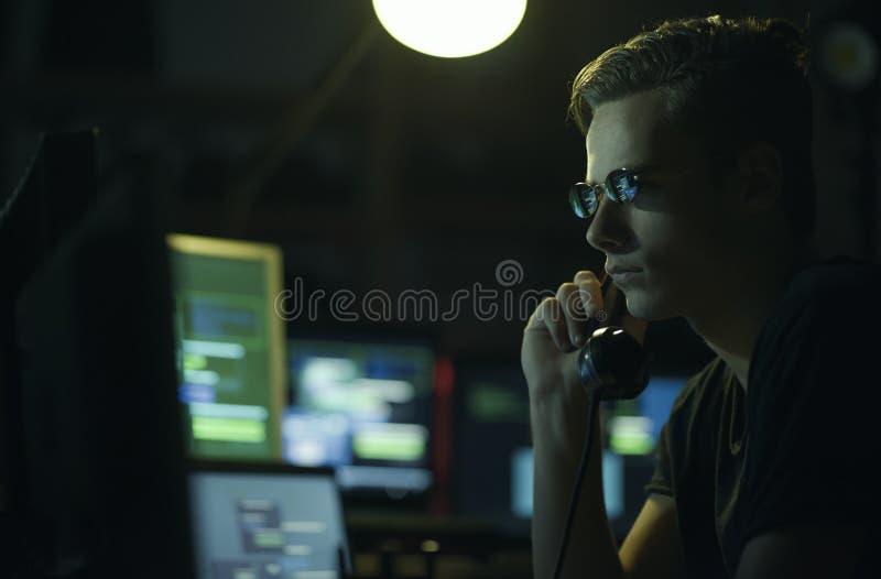 Pirata informatico che hoding un ricevitore e gli schermi di computer fotografia stock