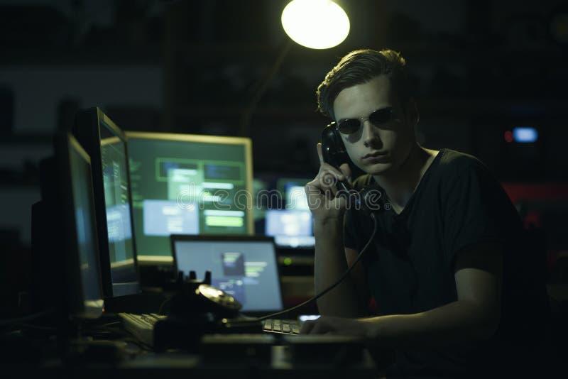 Pirata informatico che hoding un ricevitore e gli schermi di computer immagine stock