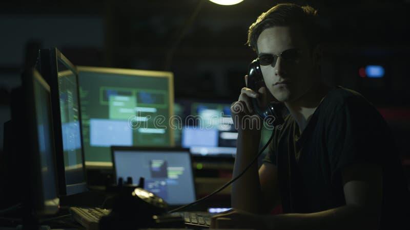 Pirata informatico che hoding un ricevitore e gli schermi di computer fotografie stock libere da diritti