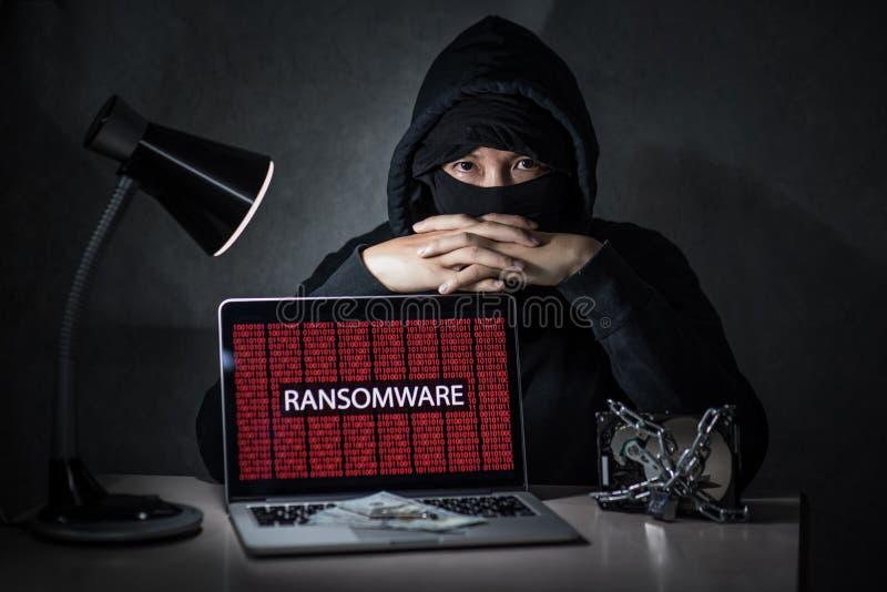 Pirata informatico con lo schermo di computer che mostra attacco del ransomware immagini stock libere da diritti