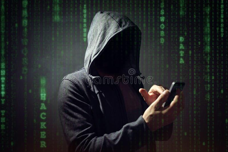 Pirata informatico di computer con il telefono cellulare fotografia stock