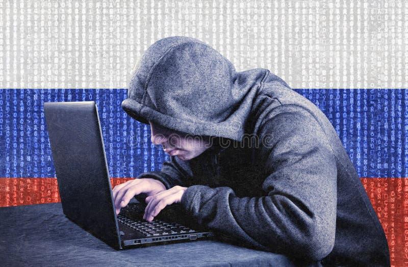 Pirata informatico di computer incappucciato russo con il computer portatile fotografie stock libere da diritti