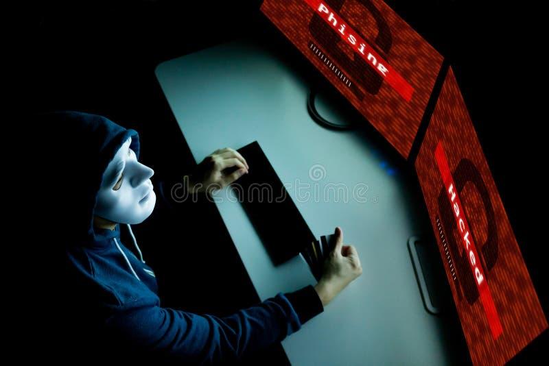Pirata informatico nella maschera sotto le vittime d'incisione e phishing del cappuccio dalle attività online di finanza e di acq fotografia stock libera da diritti