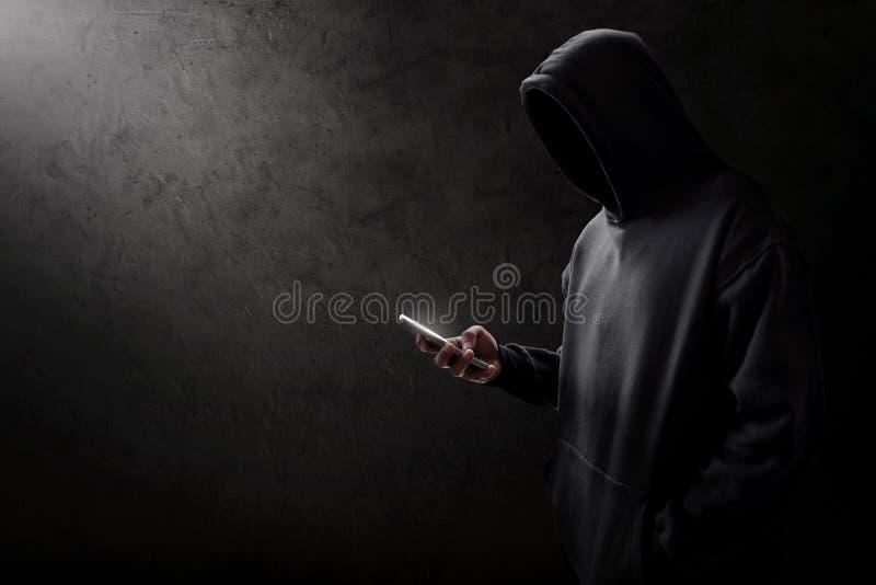 Pirata informatico sconosciuto che per mezzo del telefono cellulare immagini stock libere da diritti