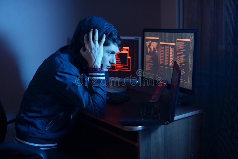 Pirata informatico in un cappuccio che pensa al problema di incisione o dell'infezione di malware sui precedenti degli schermi al fotografia stock libera da diritti