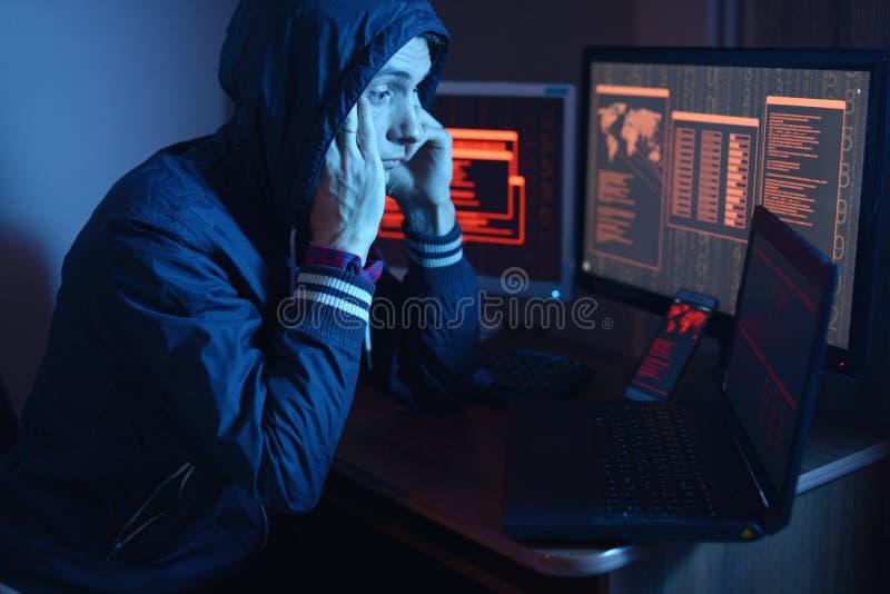 Pirata informatico in un cappuccio che pensa al problema di incisione o dell'infezione di malware sui precedenti degli schermi al fotografia stock