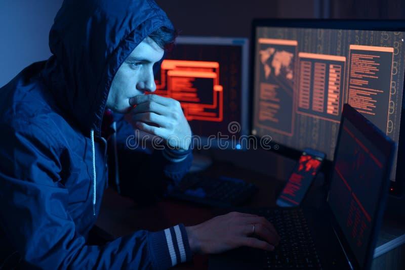 Pirata informatico in un cappuccio che pensa al problema di incisione o dell'infezione di malware sui precedenti degli schermi co immagini stock libere da diritti