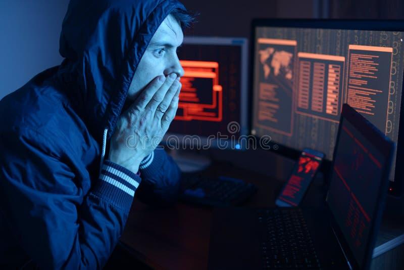 Pirata informatico in un cappuccio che pensa al problema di incisione o dell'infezione di malware sui precedenti degli schermi co immagini stock