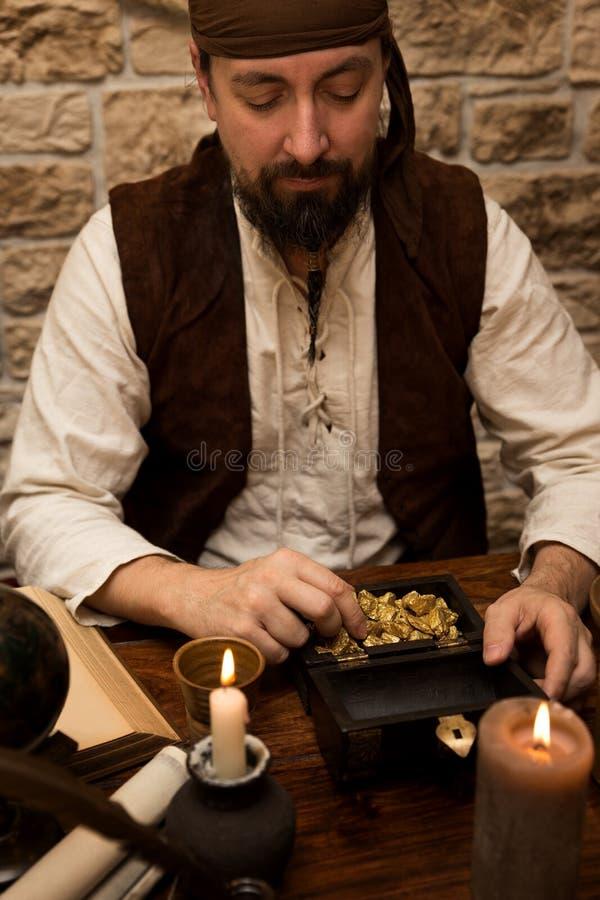 Pirate avec la grande proie, la table avec le trésor de l'or, les bougies et le v photos stock