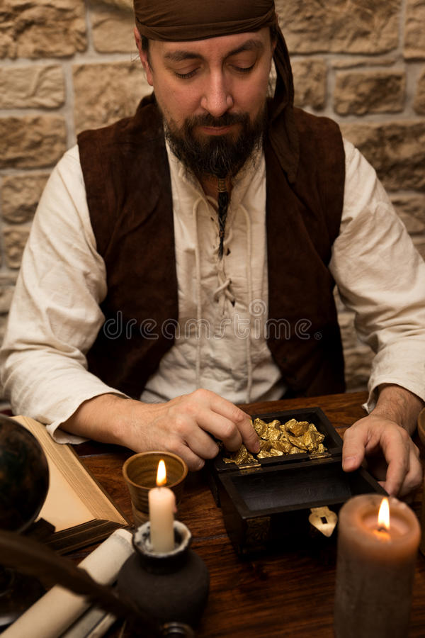 Pirate with big prey, table with treasure of gold, candles and v stock photos