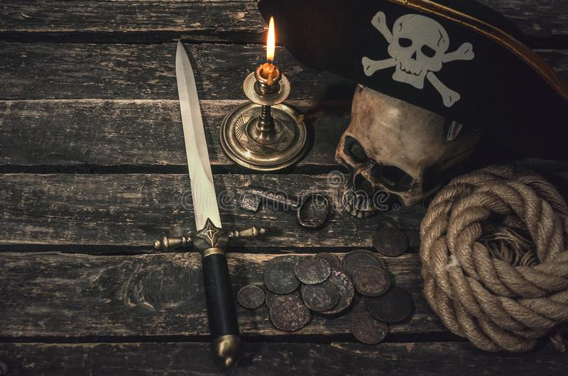 Pirate. Pirate captain table with pirate hat, human skull, dagger, treasure coins, mooring rope, burning candle and the key from treasure chest. Treasure hunter stock photos