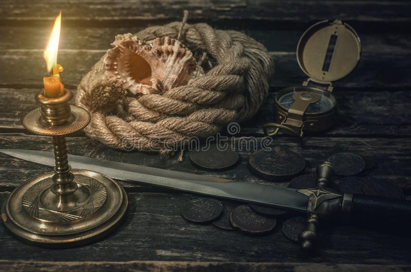 Pirate. Pirate captain table with treasure coins, mooring rope, dagger, compass, seashell and burning table. Treasure hunter concept royalty free stock images
