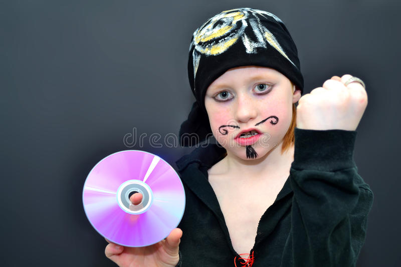 Pirate copying. Fearsome boy pirate pointing at a cd-disc and showing fist stock photos