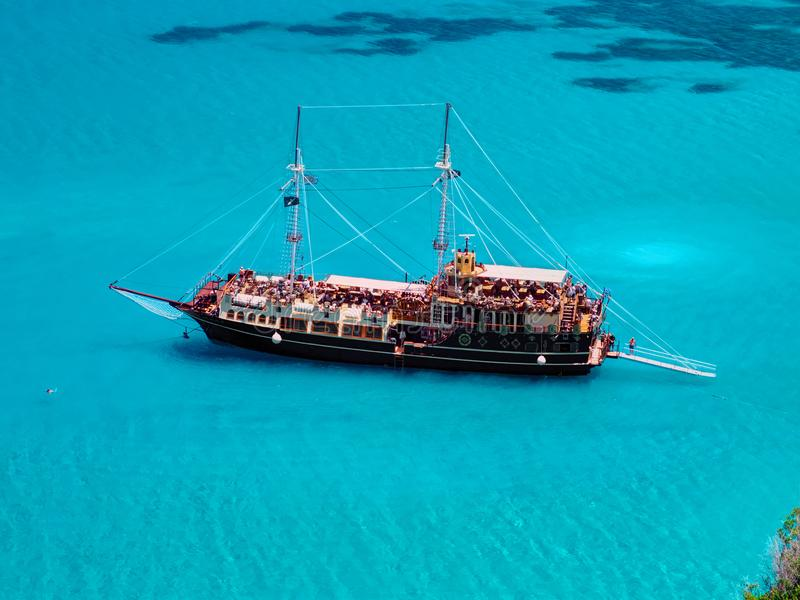 Pirate corsair style boat ship in amazing Greece island bay with swimming people, beach in Ionian Sea blue water, Greece islands h. Olidays vacations tours stock image