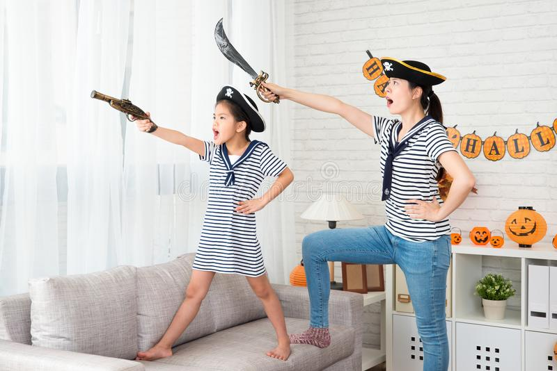 Pirate costume girl and her mother play game stock image