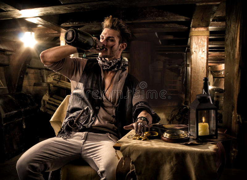 Pirate Drinking from Bottle in Ship Quarters stock photo