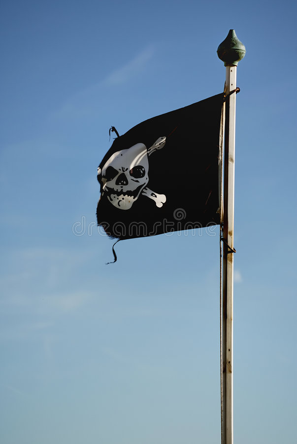 Pirate Flag. Skull and cross bones flag on a flagpole set against a blue sky stock image