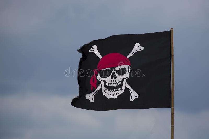 Pirate flag. On a blue sky royalty free stock photos