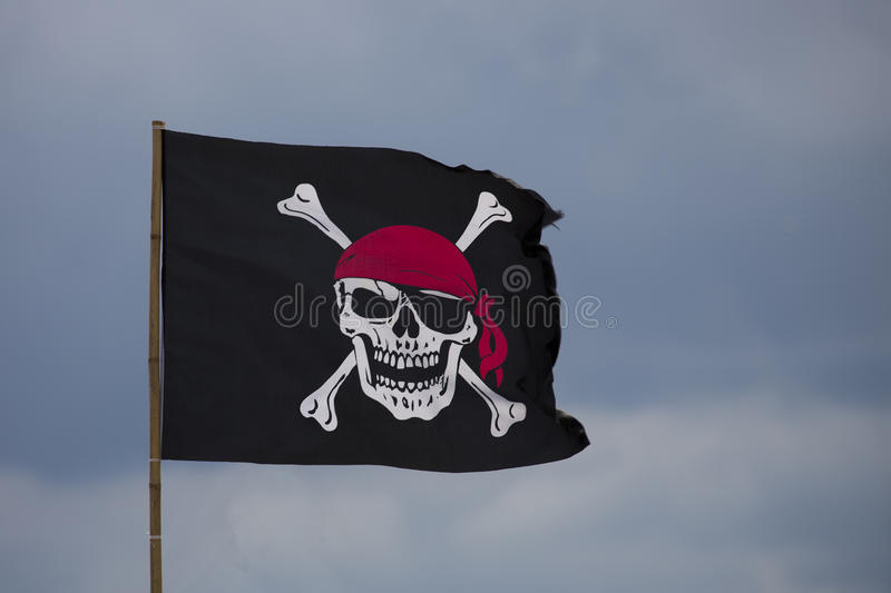 Pirate flag. On a blue sky royalty free stock photography