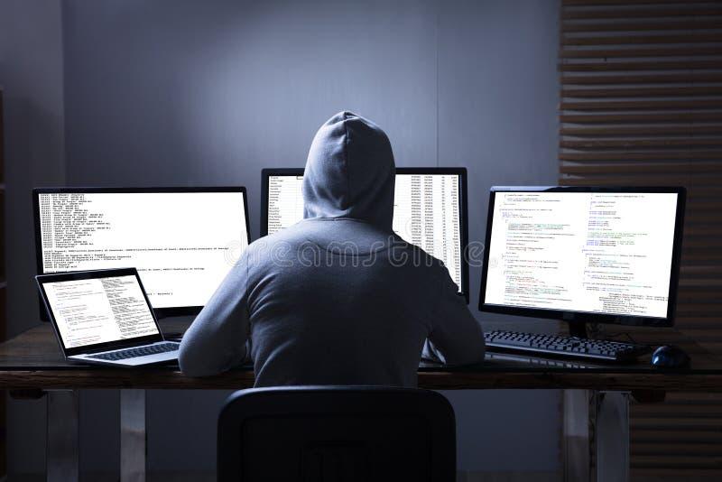 Pirate informatique à l'aide des ordinateurs multiples pour voler des données photos stock
