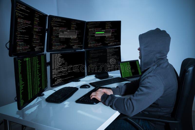 Pirate informatique à l'aide des ordinateurs pour voler des données images stock