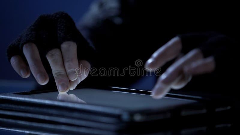 Pirate informatique à l'aide du PC de comprimé pour entailler le compte bancaire et pour voler l'argent, crime financier photo libre de droits