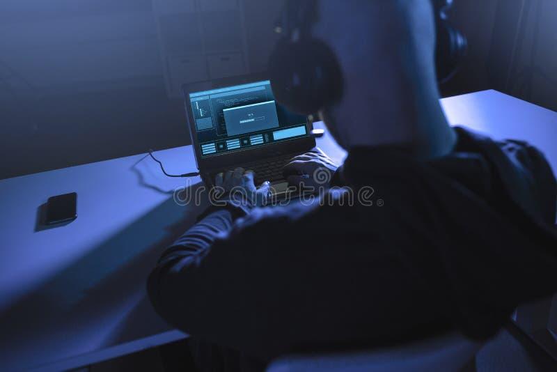 Pirate informatique avec la barre de chargement sur l'ordinateur portable dans la chambre noire image libre de droits