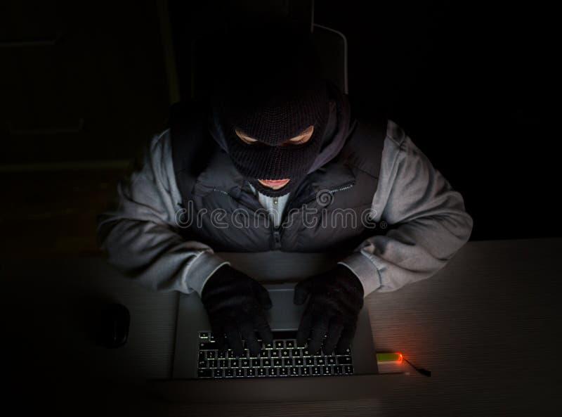 Pirate informatique avec le passe-montagne dactylographiant sur l'ordinateur portable images stock