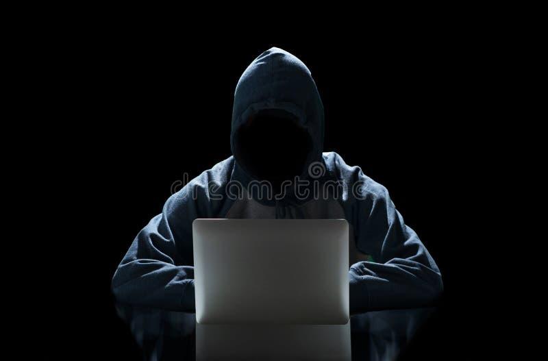 Pirate informatique dactylographiant sur un ordinateur portable d'isolement sur le fond noir avec une matrice de fond de moniteur photo libre de droits