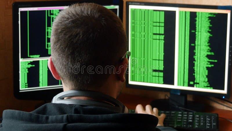 Pirate informatique en verres déchiffrant le code Système de réseau pénétrant de pirate informatique criminel de sa pièce sombre  image stock