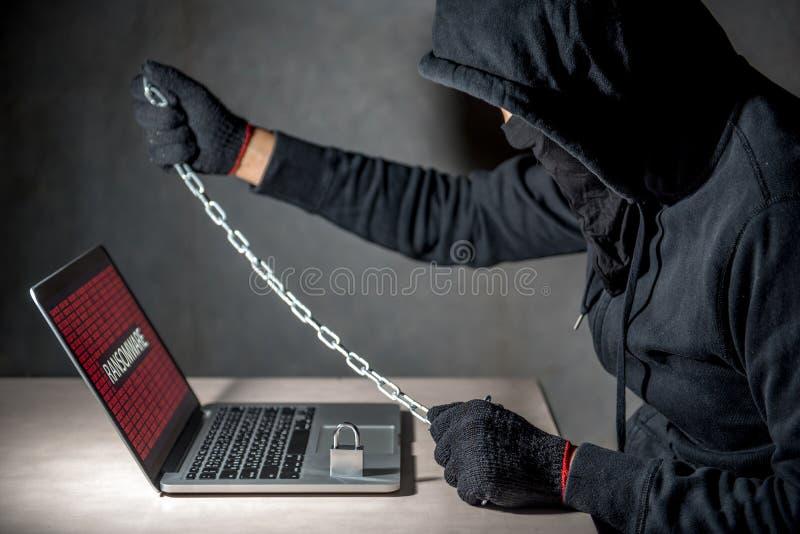 Pirate informatique masculin fermant à clef l'ordinateur à l'aide de la chaîne et du cadenas image libre de droits