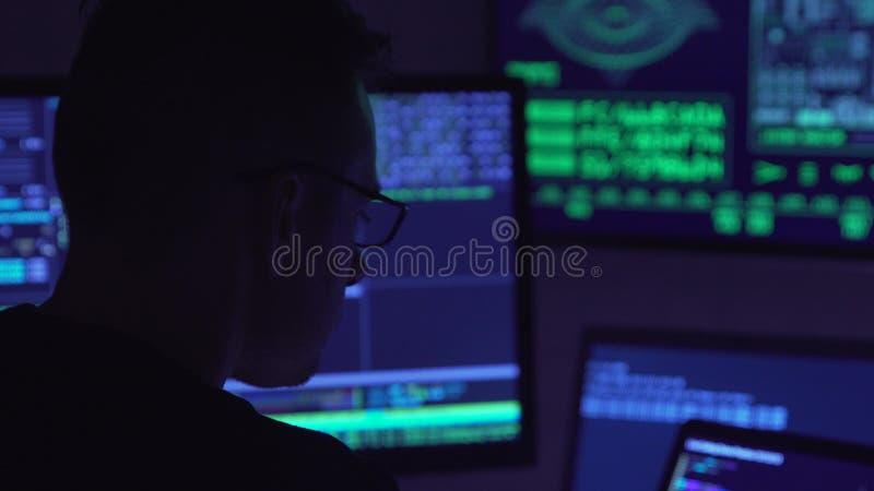 Pirate informatique masculin travaillant sur un ordinateur dans une salle sombre de bureau photo libre de droits