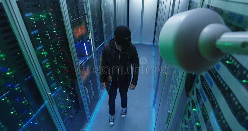 Pirate informatique masqué avec son ordinateur portable se réveillant par des rangées de serveur photos libres de droits