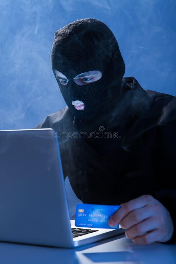 Pirate informatique tenant la carte de crédit tout en à l'aide de l'ordinateur portable photographie stock