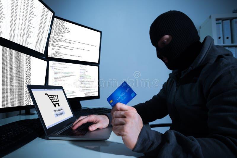 Pirate informatique tenant la carte de crédit tout en à l'aide de l'ordinateur portable au bureau photos stock