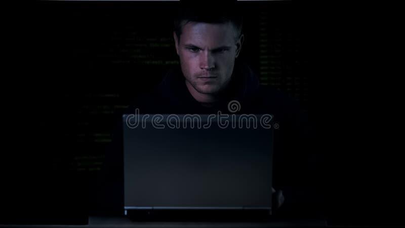 Pirate informatique travaillant à l'ordinateur portable et à la sécurité des systèmes de freinage, attaque de serveur, l'informat photo stock