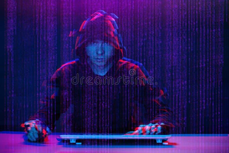 Pirate informatique travaillant avec l'ordinateur dans la chambre noire avec l'interface numérique autour Image avec l'effet de p photos stock