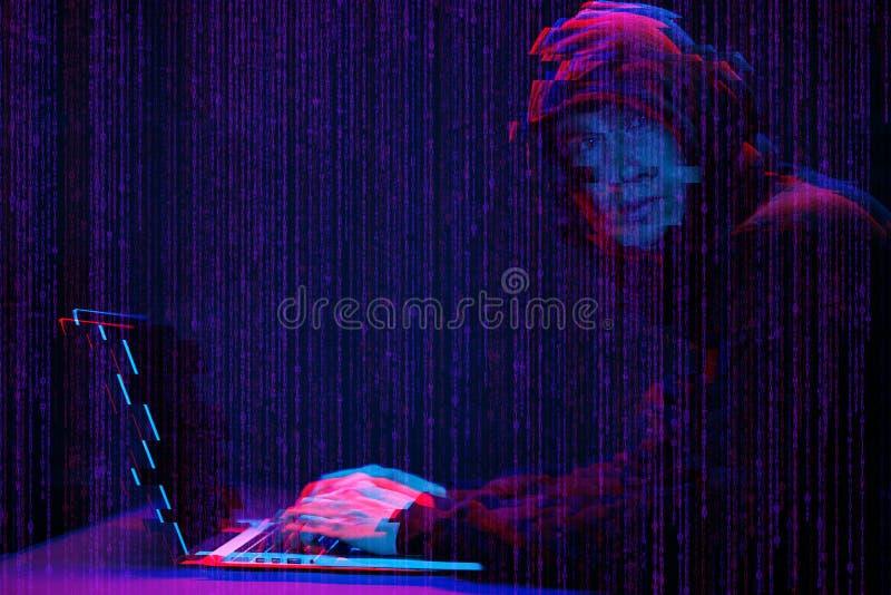 Pirate informatique travaillant avec l'ordinateur portable dans la chambre noire avec l'interface numérique autour Image avec l'e photo libre de droits