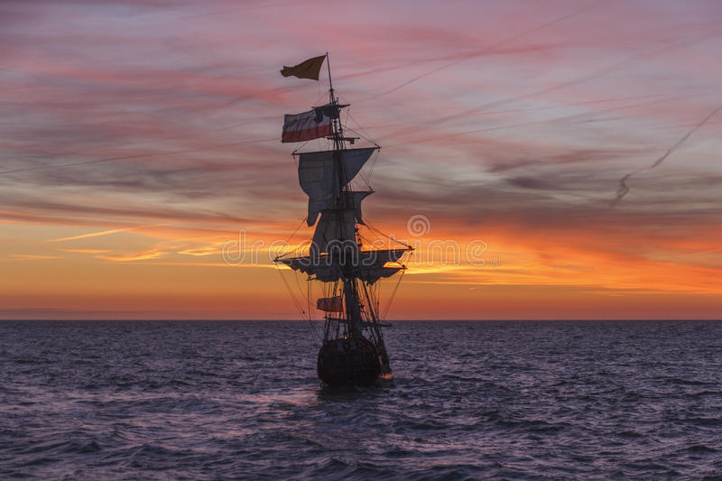 Pirate Ship. Leaving the harbor at the sunset for a long campaign against the loyal British marines stock photo