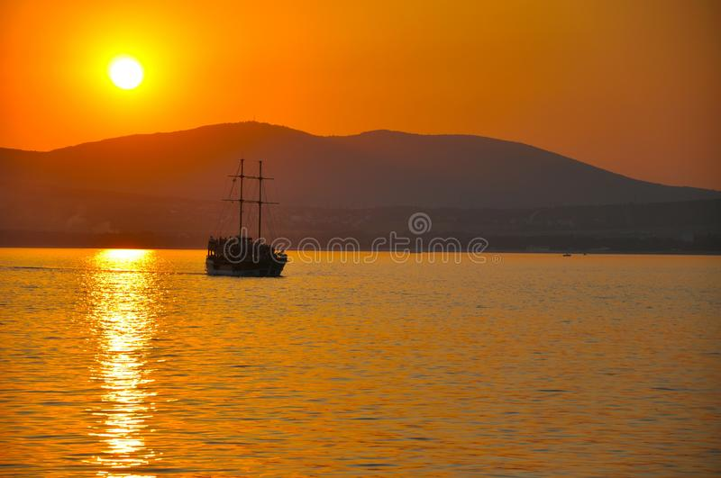 Pirate ship sailing in calm on the background of hills and sunset. Orange, travel stock photo