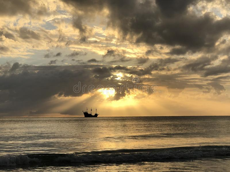 Pirate ship sailing into the sunset stock photography