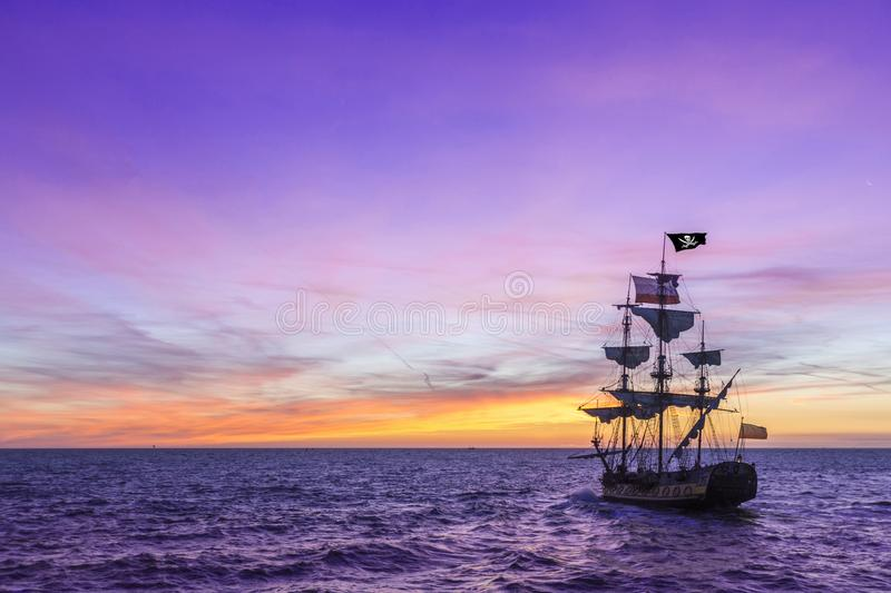 Pirate Ship under a violet sky. Pirate Ship leaving the harbor at the milky way sunset for a long campaign against the loyal marines on the oceans with place for