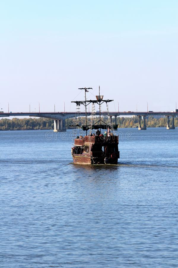 Pirate ship for a walk along the river floats to the bridge. Entertainment for tourists. royalty free stock image