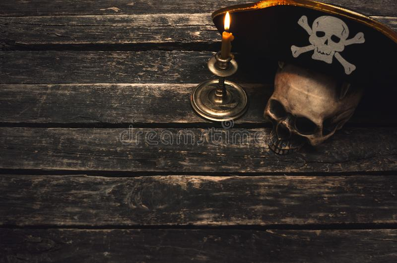 Pirate table. Pirate captain table with pirate hat, human skull and burning candle. Treasure hunter concept background stock image