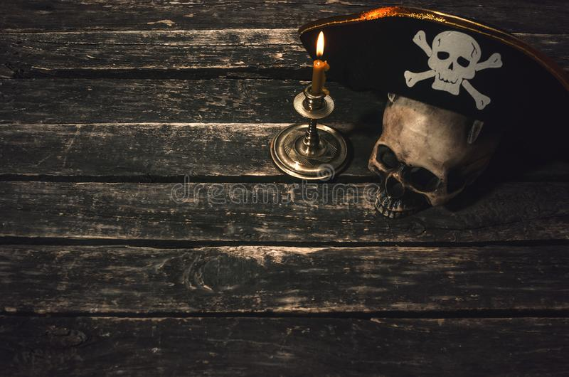 Pirate table. Pirate captain table with pirate hat, human skull and burning candle. Treasure hunter concept background royalty free stock images