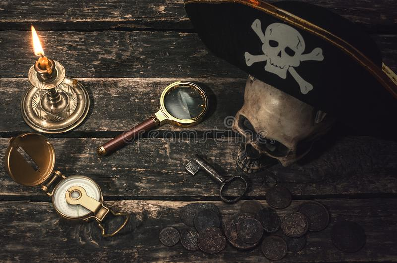 Pirate table. Pirate captain table with pirate hat on the human skull, compass, magnifying glass, mooring rope, coins, key of treasure chest and burning table stock photos