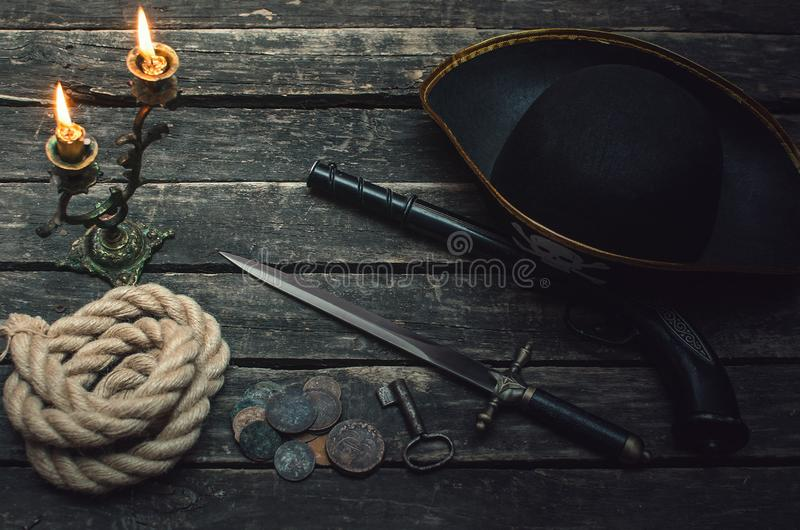 Pirate table. Pirate captain table with pirate hat, mooring rope, weapon, coins, key of treasure chest and burning candle. Treasure hunter concept royalty free stock image
